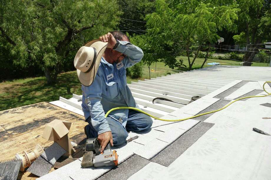 Marcial Gutierrez wipes sweat from his brow as he works to install a roof  July 5