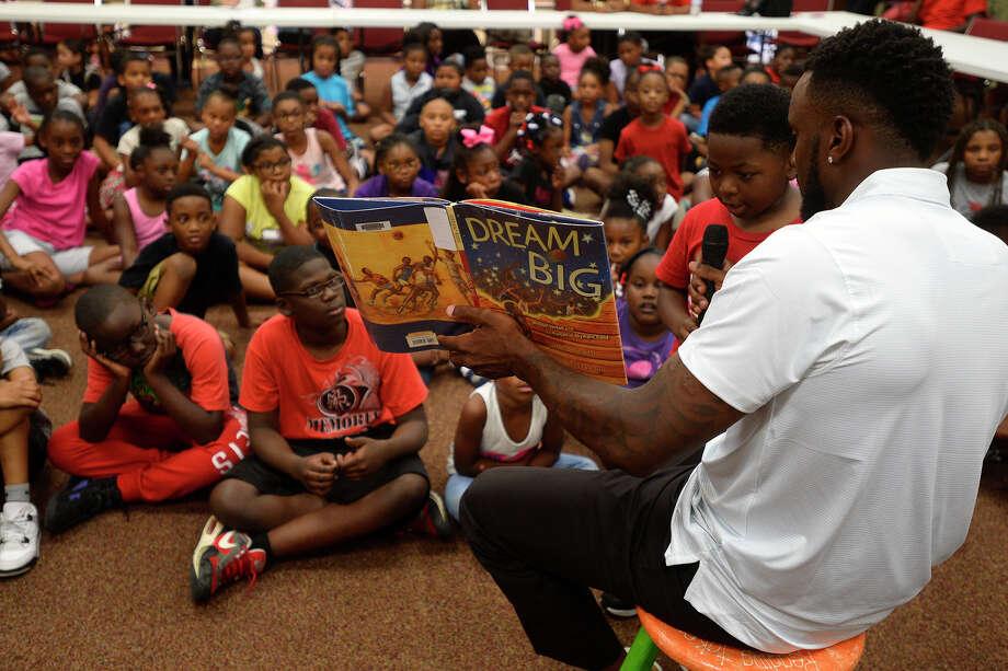 Retired NFL player Jordan Babineaux, a native of Port Arthur, reads to children at the Port Arthur Public Library on Wednesday.  Photo taken Wednesday 7/6/16 Ryan Pelham/The Enterprise Photo: Ryan Pelham / ©2016 The Beaumont Enterprise/Ryan Pelham