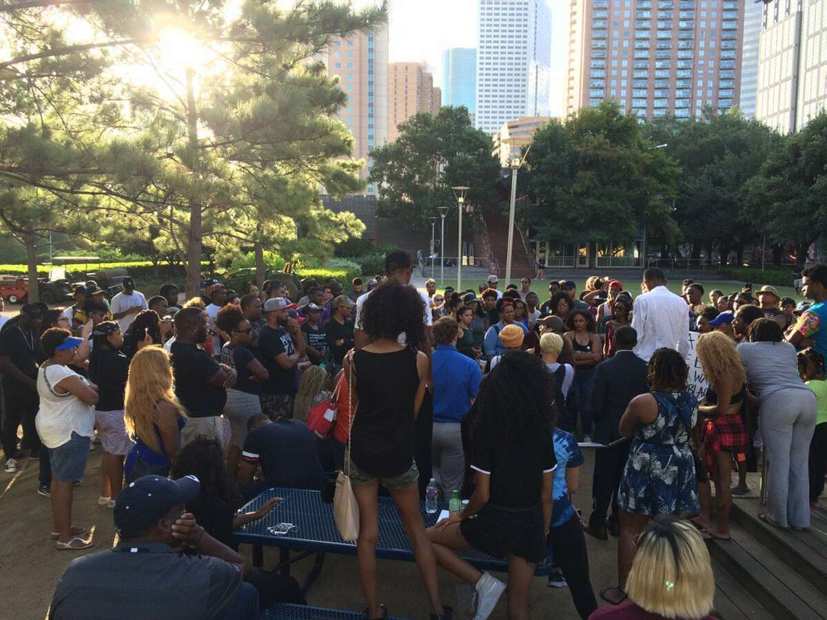 Chantz Alexander Smith, in the white shirt at right, listens at a Wednesday gathering he organized at Discovery Green. A rally planned there for 6 p.m. Saturday will continue in the wake of the Dallas shootings of 11 police officers, Smith said Friday.