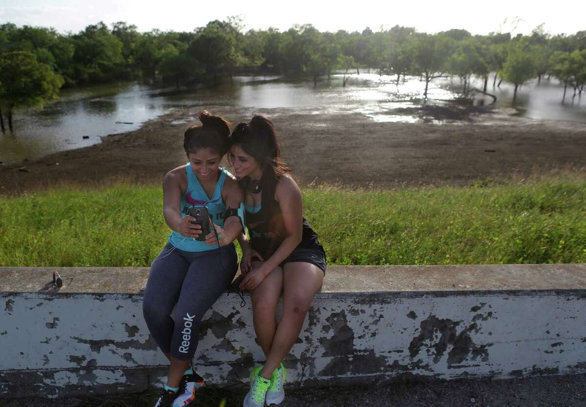 Sisters Gloria Almaraz, left, and Doris Alvarenga rest during a run near the Barker Reservoir on Wednesday.