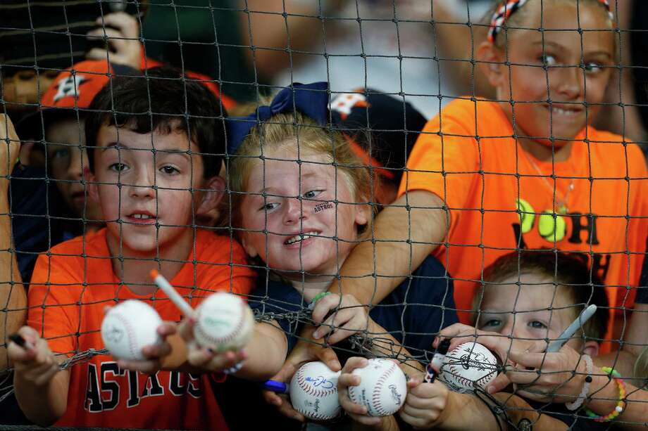 Elise Koenig, 8, reaches through the netting as she sought to get Colby Rasmus' autograph during batting practice before the start of an MLB baseball game at Minute Maid Park, Wednesday, July 6, 2016, in Houston. Photo: Karen Warren, Houston Chronicle / © 2016 Houston Chronicle