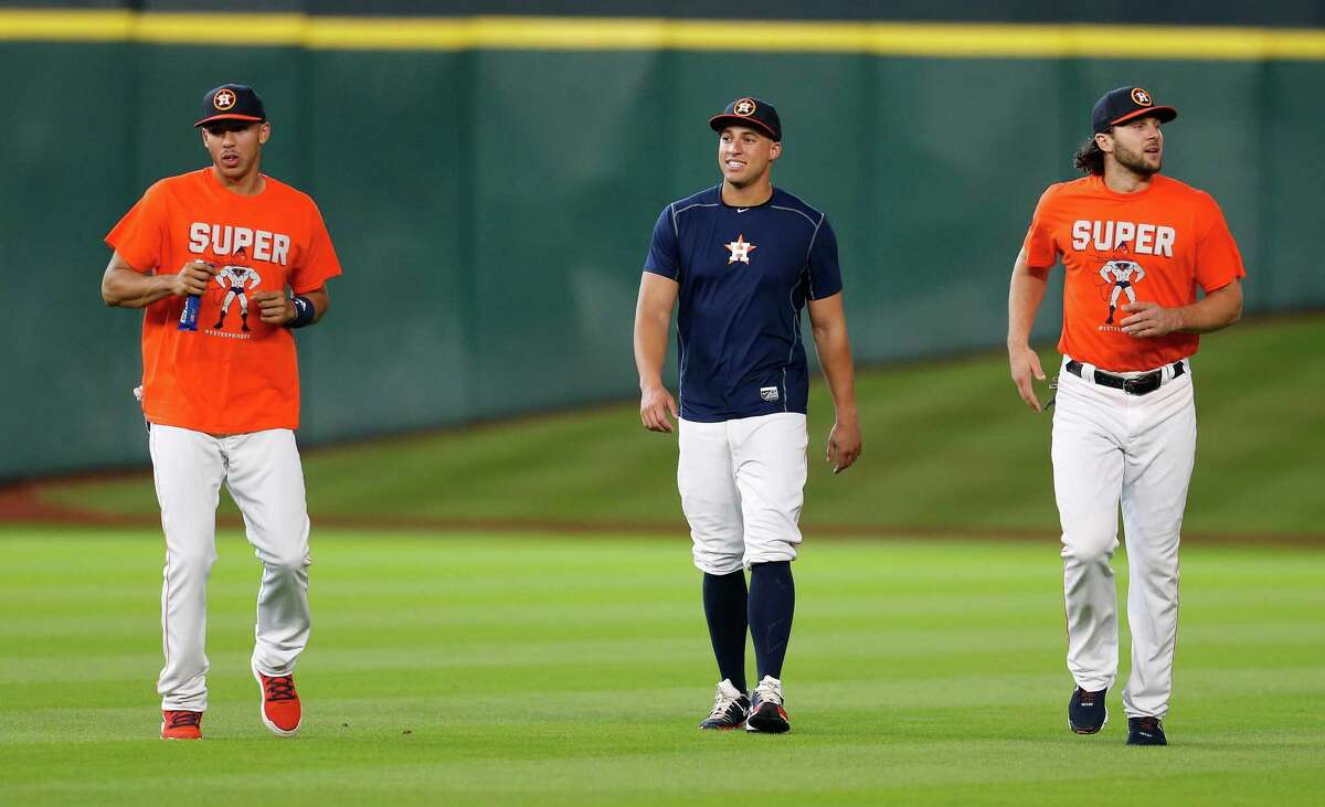 Houston Astros Carlos Correa and Jake Marisnick wear their #votespringer t-shirts as they walk with George Springer during batting practice before the start of an MLB baseball game at Minute Maid Park, Wednesday, July 6, 2016, in Houston.