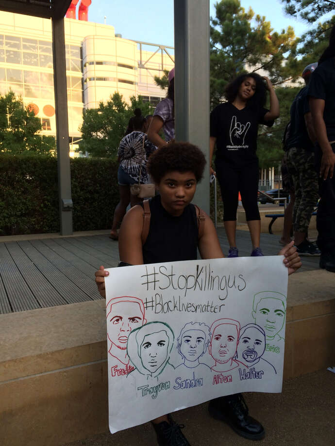 """At the Discovery Green event, Angelica McGinnis, 17, shows a sign she drew that includes figures central to the Black Lives Matter movement protesting police shootings of minorities. Of the gathering, she said, """"I feel like this is a good start."""""""