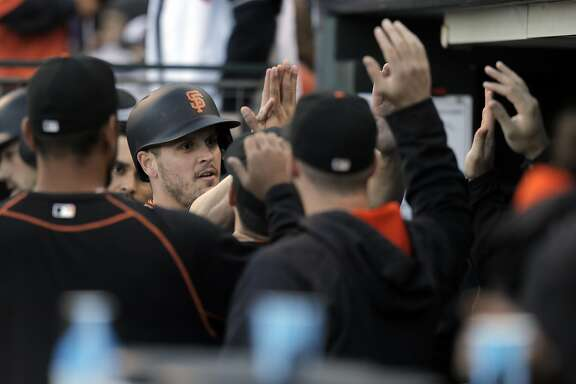 Grant Green (38) is high fived after scoring on a Brandon Belt triple in the first inning as the San Francisco Giants played the Colorado Rockies at AT&T Park in San Francisco, Calif., on Wednesday, July 6, 2016.