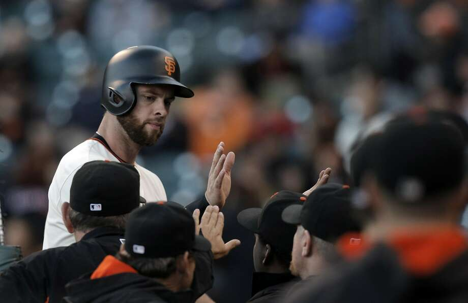 Brandon Belt gets congratulated after scoring against the Colorado Rockies on July 6 at AT&T Park. Photo: Carlos Avila Gonzalez, The Chronicle