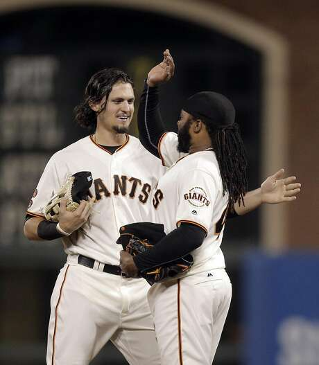 Outfielder Jarrett Parker  congratulates Johnny Cueto after the Giants starter threw his fourth complete game of the season Wednesday against the Colorado Rockies. Photo: Carlos Avila Gonzalez, The Chronicle