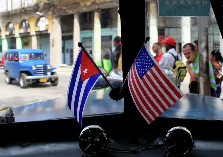 In this March 22, 2013 file photo, miniature flags representing Cuba and the U.S. are displayed on the dash of a classic American car in Havana, Cuba.From Hemingway to Rihanna, take a look back at some of the stars how have spent time in Cuba. Photo: Franklin Reyes, STR / AP