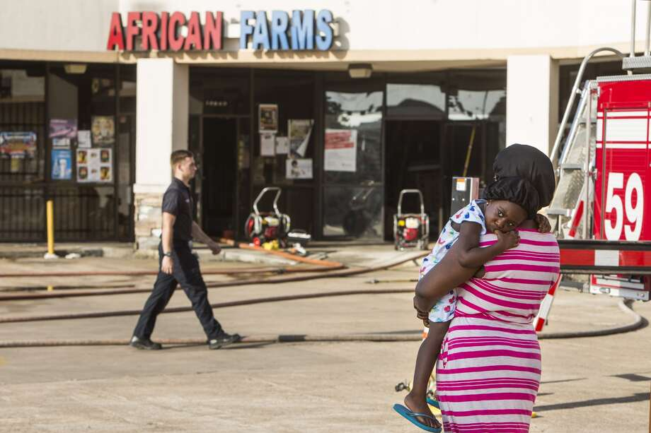 A woman stands outside African Farms, in a strip center in the 12000 block of Fondren, after a fire broke out in the business on Thursday, July 7, 2016, in Houston. ( Brett Coomer / Houston Chronicle )