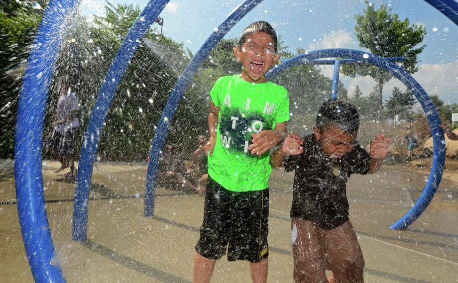 Jeremy Orellanas, 5, and his uncle, Angel Orellanas, 4, beat the heat by playing at the splash park at Devon's Playground in Norwalk on Wednesday as a heat advisory takes effect this week. Photo: Erik Trautmann / Hearst Connecticut Media / Norwalk Hour