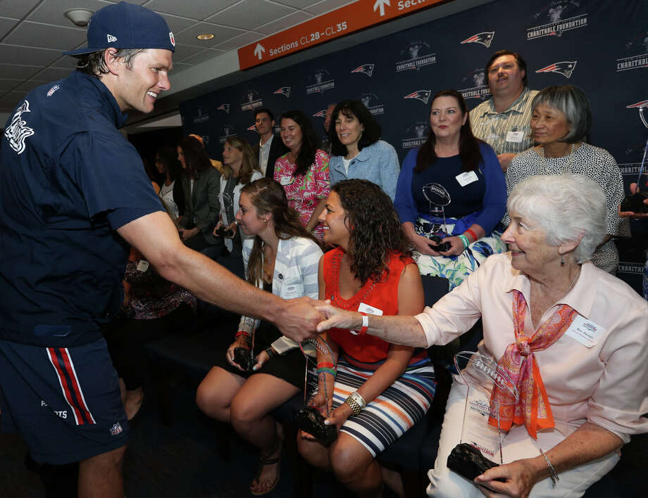 Literacy Volunteers on the Green in New Milford co-founder and tutor Rita Guariglia was recently presented a $10,000 Myra Kraft Community MVP Award. On hand to congratulate her, right, was New England Patriot player Tom Brady. Photo: Contributed Photo / The News-Times Contributed