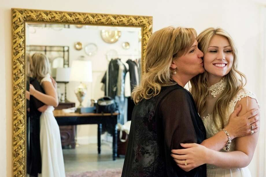 Sue LaBonville of Sanford kisses her daughter Cassie as they pose for a photo at Blue Gardenia Bridal Boutique in Midland on June 9.  'We have a really special bond. We're best friends,' Cassie LaBonville said of her mother. / ©2016