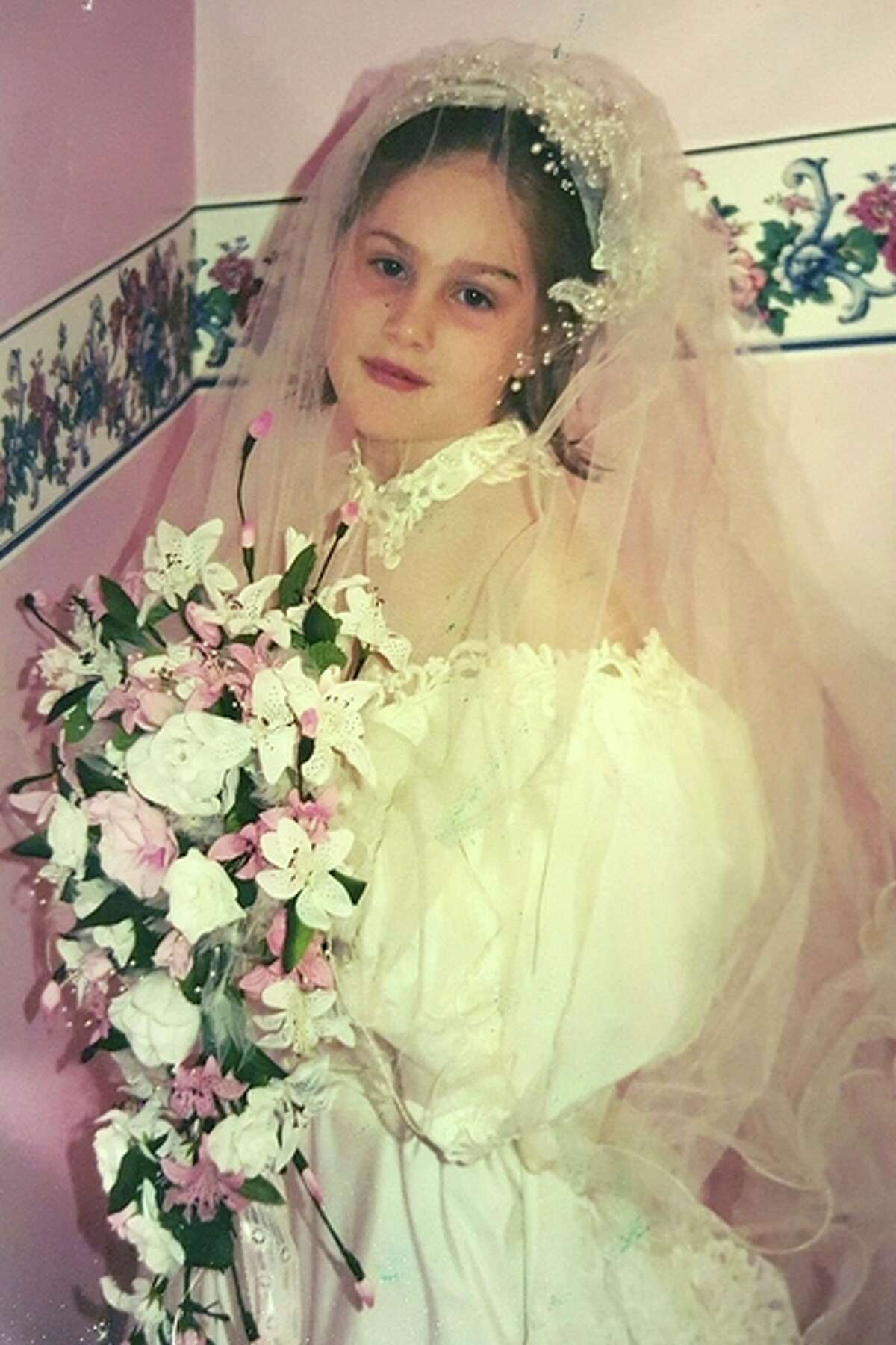 At age 5, Cassie LaBonville, 5, poses for a photo while wearing her mother 's wedding dress and veil. Photo provided.