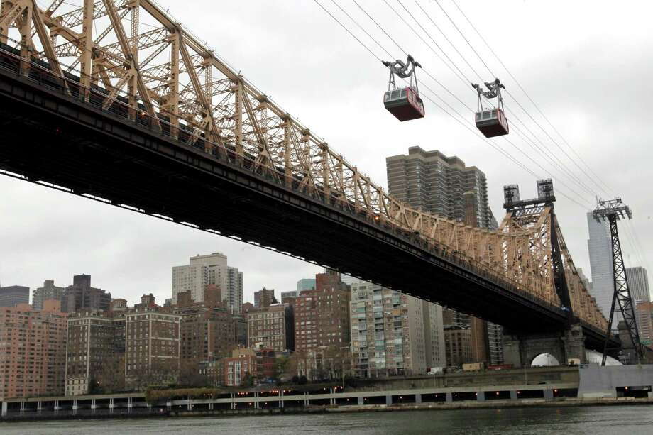 The Roosevelt Island trams are framed by the Queensboro Bridge and the Manhattan skyline as they make their way over the East River into Roosevelt Island, Tuesday, Nov. 30, 2010, in New York. (AP Photo/Mary Altaffer) Photo: Mary Altaffer / AP2010