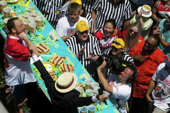 Joey Chestnut celebrates winning the 2016 Nathan's Famous Hot Dog Eating Contest in the Coney Island neighborhood of New York. Judge Ken Hoffman, next to cameraman, looks on.