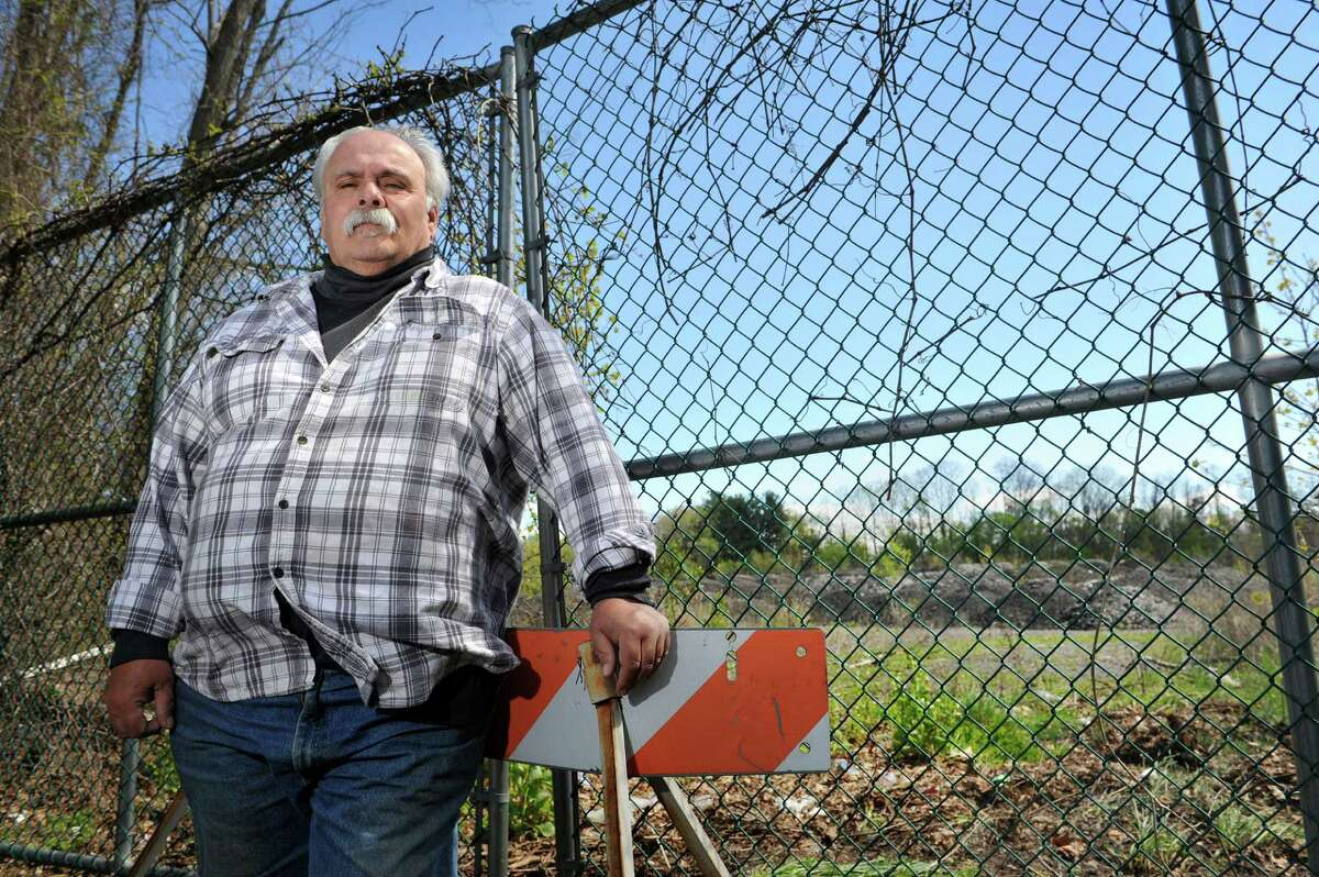 Marc Della Villa stands near a gate that leads into the Cheltingham landfill on Monday, May 9, 2016, in Schenectady, N.Y. Della Villa grew up in the area and said the former Schenectady International factory and the landfill, which the factory allegedly dumped in, sickened many neighbors over the years. (Paul Buckowski / Times Union)