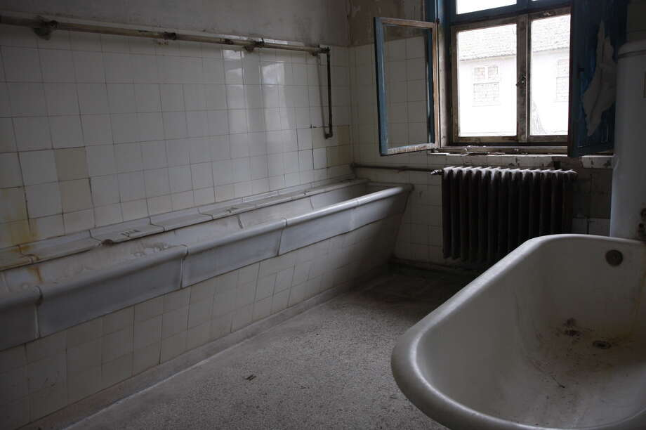 """Deserted houses for the athletes in the former Olympic Village. An abandoned bathroom at the """"Jesse Owens House"""" Photo: Ullstein Bild/ullstein Bild Via Getty Images"""