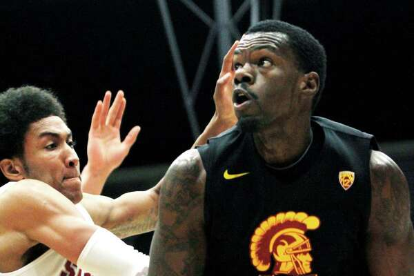 Southern California's Dewayne Dedmon (14) looks up to shoot as Stanford's Josh Huestis defends during the first half of an NCAA college basketball game in Stanford, Calif., Thursday, Feb. 14, 2013. (AP Photo/George Nikitin)