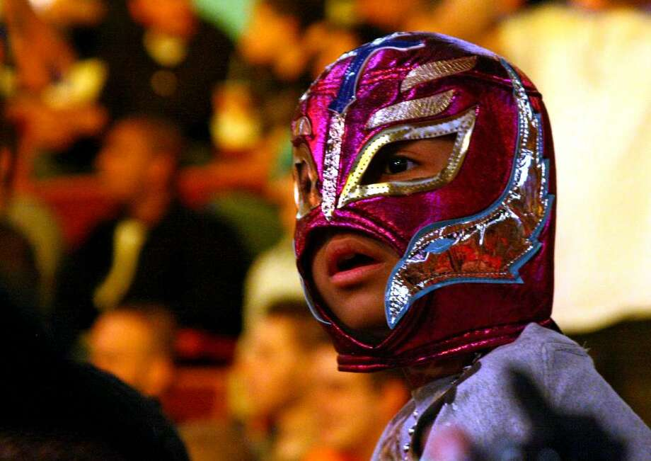 Aran Cruz, 7, of Poughkeepsie, NY, watches the wrestling action, during WWE's Smackdown event at Mohegan Sun in Uncasville, Conn. on Tuesday April 20, 2010. The mask Aran is wearing is of his favorite masked wrestler, Rey Mysterio. Photo: Christian Abraham / Connecticut Post no sale