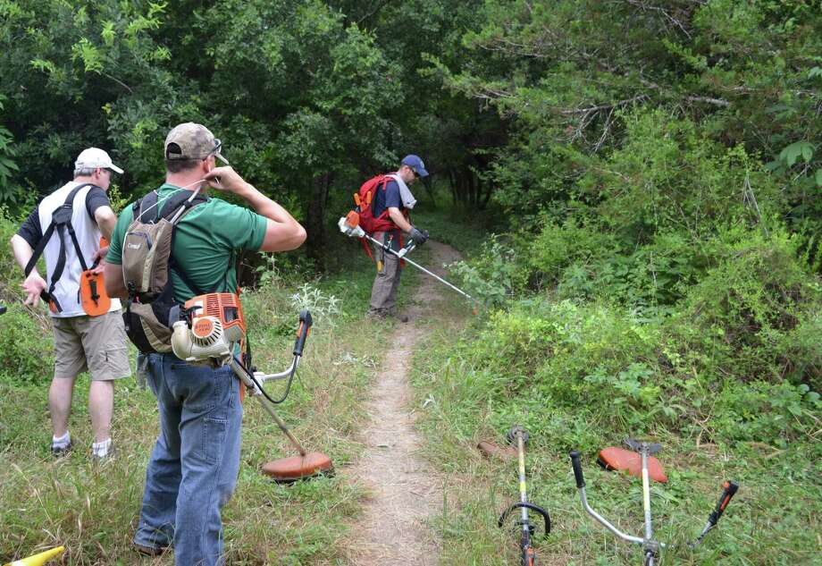 People camp at Government Canyon State Natural Area — and for others it's more than camping. It's a magical moment with a family member. Here, volunteers prepare to help open up an overgrown trail at the site. Photo: Ralph Winingham /For The Express-News