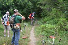 People camp at Government Canyon State Natural Area — and for others it's more than camping. It's a magical moment with a family member. Here, volunteers prepare to help open up an overgrown trail at the site.