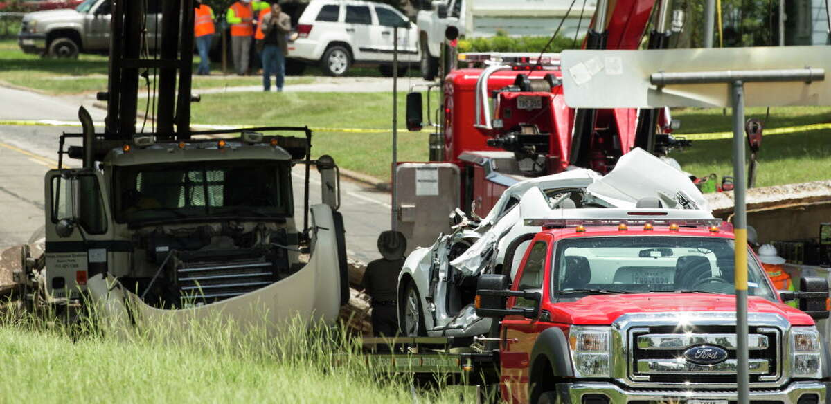 A crushed car, right, and a truck sit near a bridge that collapsed on Thursday, July 7, 2016, in Sealy. Police said a truck hit the bridge causing a portion of it to collapse onto a passing car, killing a 12-year old child. The collapse occurred about 10 a.m. on U.S. 90 near Texas 36, according to the Sealy Police Department.