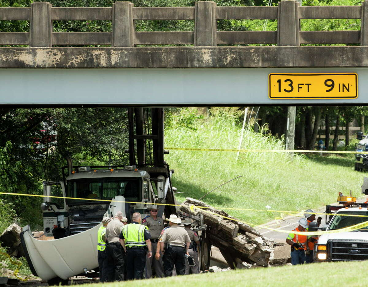 Police and Texas Department of Transporation officials investigate the scene of a bridge collapse on Thursday, July 7, 2016, in Sealy. Police said a truck hit the bridge causing a portion of it to collapse onto a passing car, killing a 12-year old child. The collapse occurred about 10 a.m. on U.S. 90 near Texas 36, according to the Sealy Police Department.