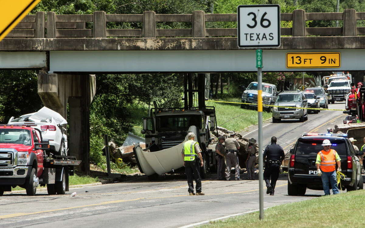 A crushed car, left, and a truck sit near a bridge that collapsed on Thursday, July 7, 2016, in Sealy. Police said a truck hit the bridge causing a portion of it to collapse onto a passing car, killing a 12-year old child. The collapse occurred about 10 a.m. on U.S. 90 near Texas 36, according to the Sealy Police Department.