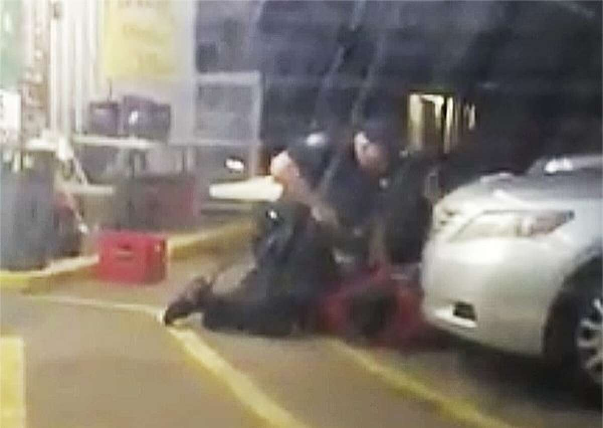 In this July 5 photo made from video, Alton Sterling is held by two Baton Rouge police officers, with one holding a hand gun, outside a convenience store.