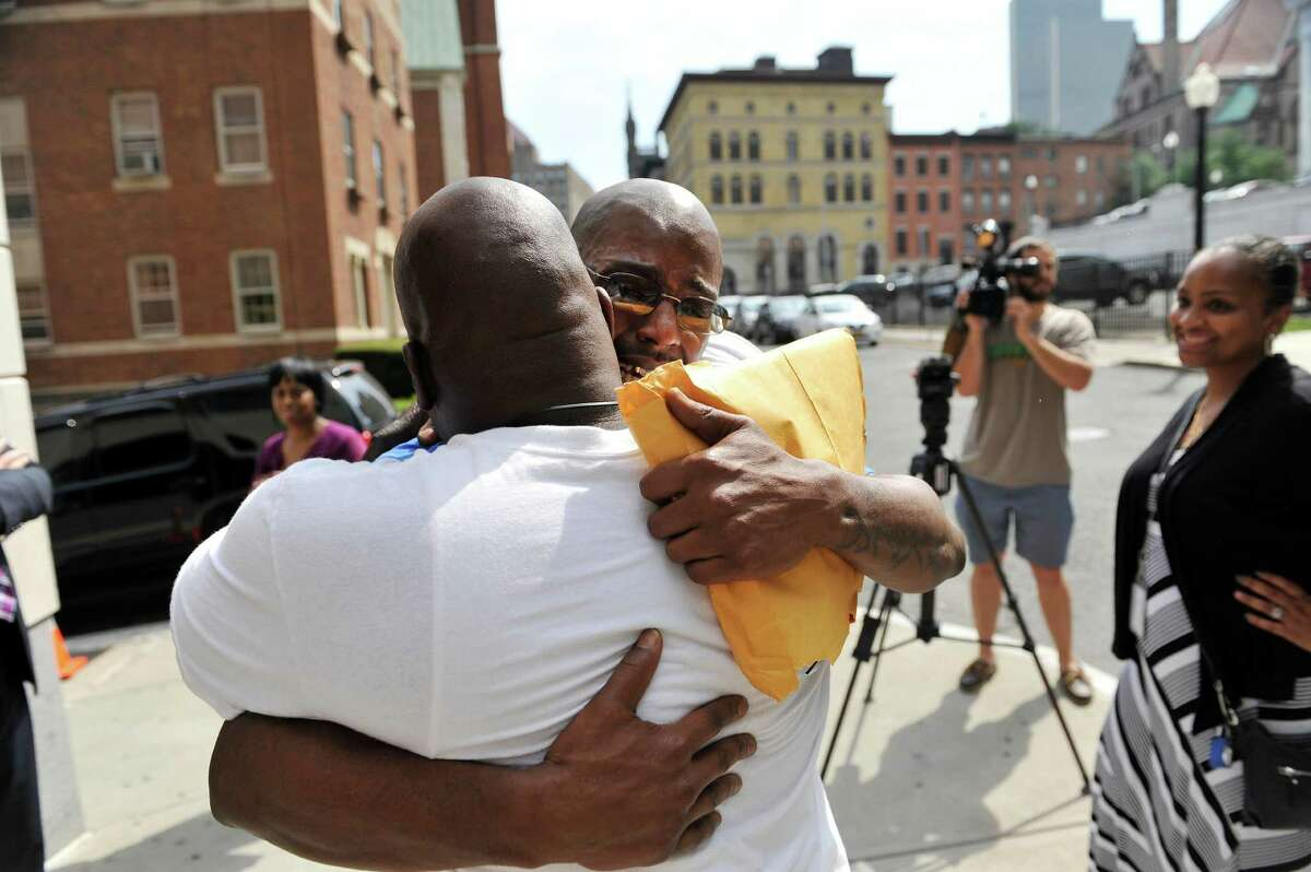 Carl Dukes, right, hugs his cousin, Jamal Hameed outside the Albany County Judicial Center on Thursday, July 7, 2016, in Albany, N.Y. Dukes, who was imprisoned for the 1997 killing of Erik Mitchell, a University at Albany student, was exonerated of the crime. Another man has been implicated in the killing. (Paul Buckowski / Times Union)