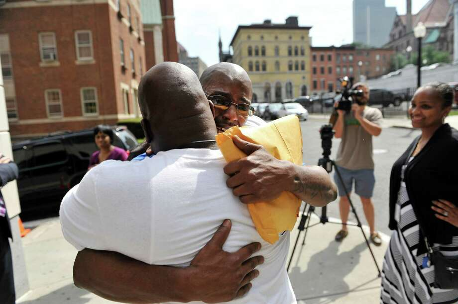 Carl Dukes, right, hugs his cousin, Jamal Hameed outside the Albany County Judicial Center on Thursday, July 7, 2016, in Albany, N.Y.  Dukes, who was imprisoned for the 1997 killing of Erik Mitchell, a University at Albany student, was exonerated of the crime.  Another man has been implicated in the killing.   (Paul Buckowski / Times Union) Photo: PAUL BUCKOWSKI / 20037263A