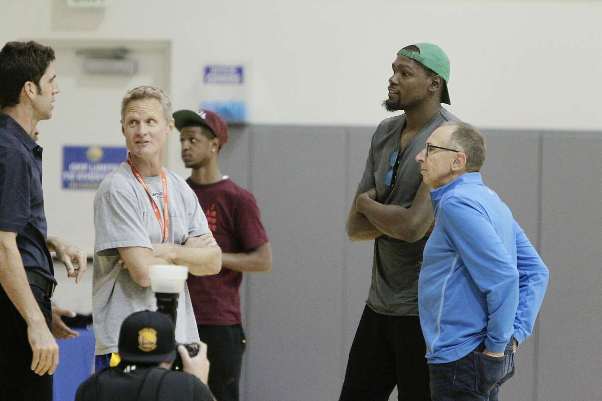Kevin Durant (second from right in green hat) talks with Bob Myers (left), Warriors general manager, Steve Kerr (second from left), Warriors head coach, and Ron Adams (right), Warriors assistant coach, before the introductory press conference for Durant at the Warriors practice facility on�Thursday, July 7, 2016 in Oakland, California.