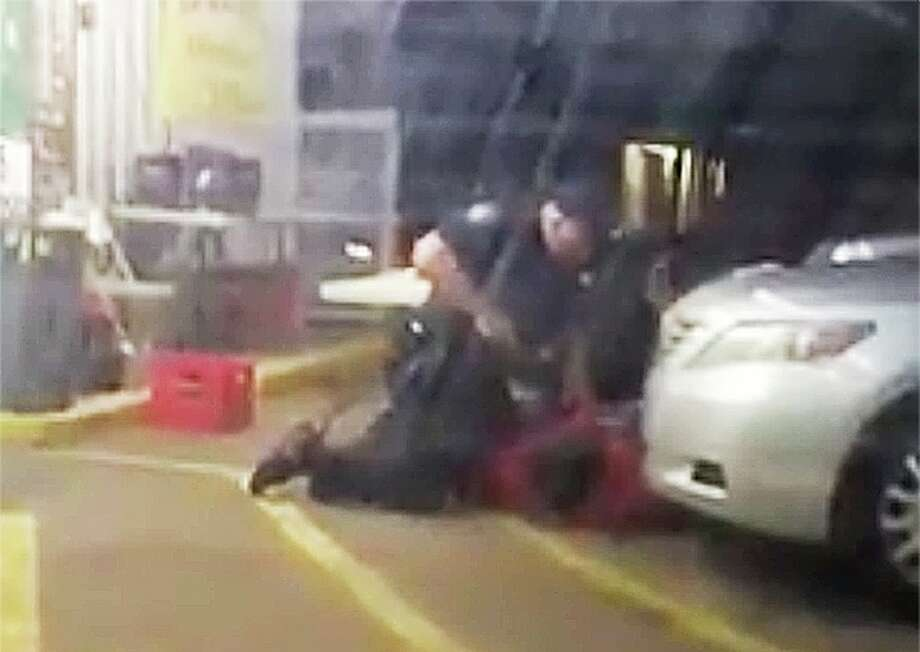 In this Tuesday, July 5, 2016 photo made from video, Alton Sterling is held by two Baton Rouge police officers, with one holding a hand gun, outside a convenience store in Baton Rouge, La. Moments later, one of the officers shot and killed Sterling, a black man who had been selling CDs outside the store, while he was on the ground. (Arthur Reed via AP) Photo: Arthur Reed / Associated Press / Arthur Reed