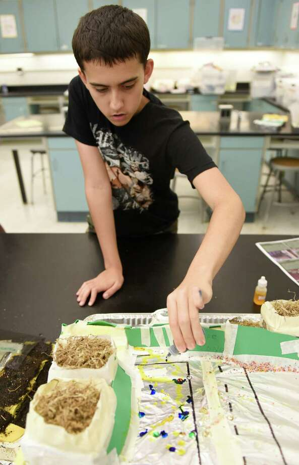 "Nick Ksiazek, an incoming ninth-grader simulates polluting his city to test for chemical runoff in the Engineering Urban Landscapes summer class at Central Greenwich Middle School in Greenwich, Conn. Wednesday, July 6, 2016. Students in the class designed the layout of their cities in a water that would keep the water supply from being polluted with chemical runoff after ""rainstorms"" with a water spray bottle. Photo: Tyler Sizemore / Hearst Connecticut Media / Greenwich Time"