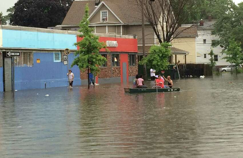People row down Iranistan Avenue near the intersection of State Street in Bridgeport, Conn. after heavy rain pounded the area on Thursday, July 7, 2016. Multiple reports of fallen trees and some flooding were recieved by police and fire services who scrambled to assist drivers.