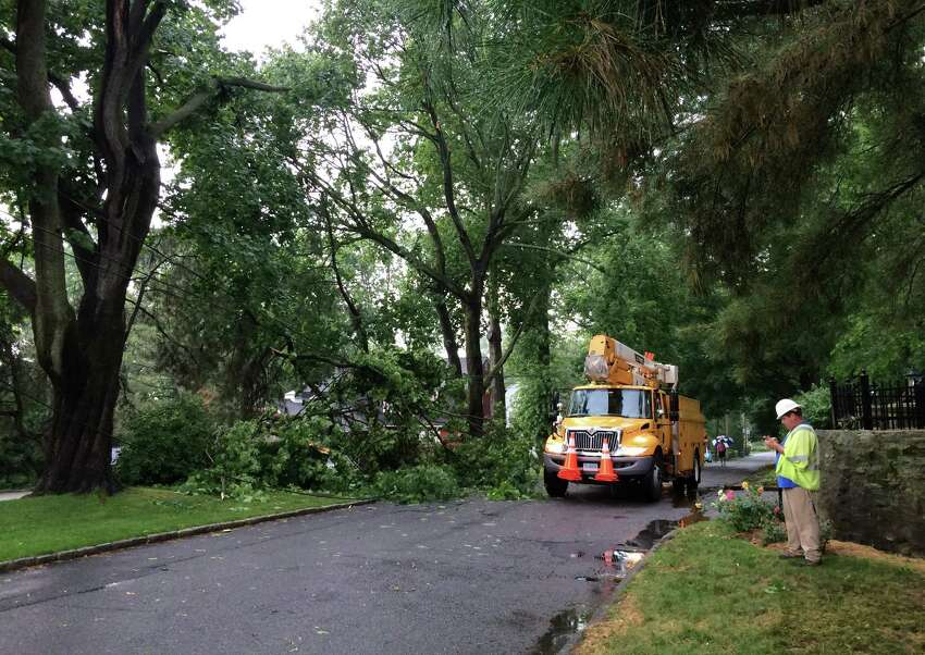 Workers on the scene in of downed wires and tree limbs on Sailors Lane in the Black Rock section of Bridgeport, Conn. on Thursday, July 7, 2016. Heavy wind and rain pounded the area resulting in multiple reports of fallen trees and flooding.