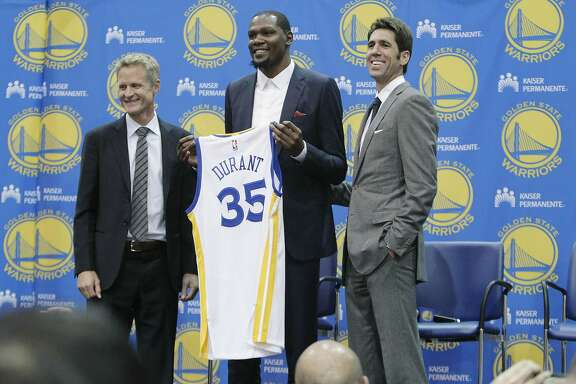 Kevin Durant (center) stands with Steve Kerr (left), Warriors head coach and Bob Myers, (right) Warriors general manager, as he holds a Warriors jersey during the introductory press conference for Durant at the Warriors practice facility on Friday, July 7, 2016 in San Francisco, California.