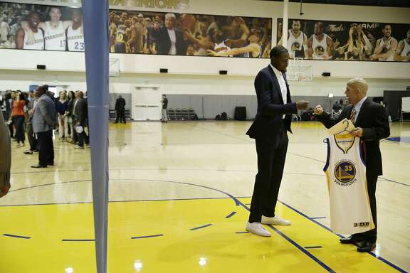 Kevin Durant (second from right) fist bumps Raymond Ridder (right) , Warriors Communications vice president , before the introductory press conference for Durant at the Warriors practice facility on�Thursday, July 7, 2016 in Oakland, California.