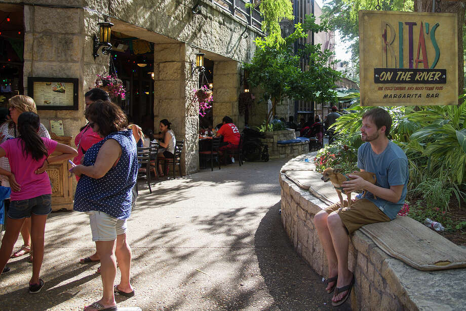 Zach Mach pets his dog, Biscuit, while they wait for a table at Rita's on the River. Photo: Alma E. Hernandez /For The San Antonio Express-News