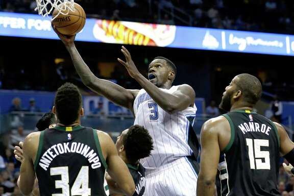 Orlando Magic's Dewayne Dedmon (3) gets past Milwaukee Bucks' Giannis Antetokounmpo (34) and Greg Monroe (15) during the second half on April 11, 2016, in Orlando, Fla.