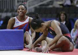 Simone Biles, left, smiles next to Gabrielle Douglas while stretching during practice at the U.S. Olympic trials in gymnastics in San Jose, Calif., Thursday, July 7, 2016. (AP Photo/Jeff Chiu)