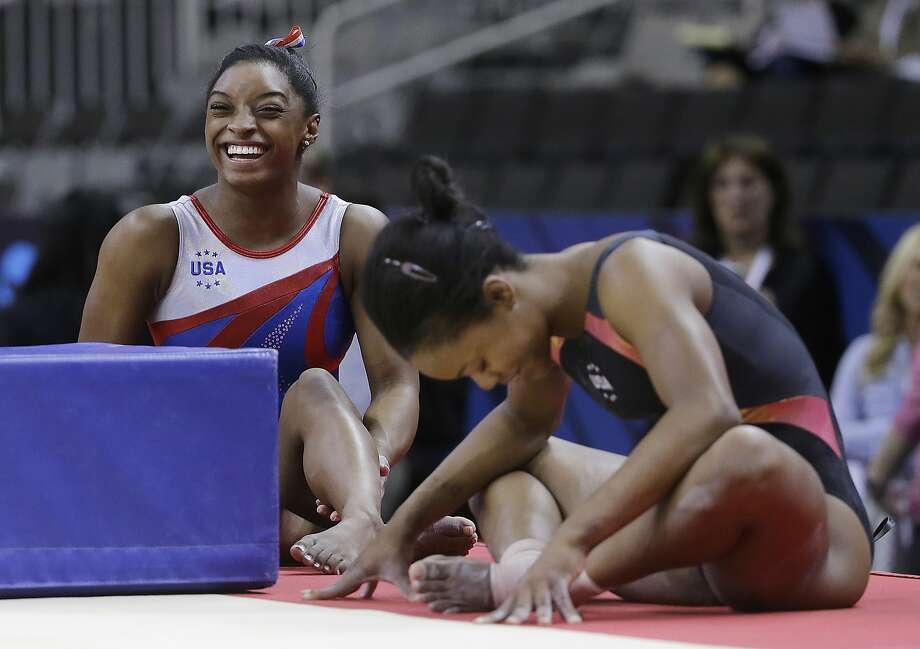 Simone Biles, left, smiles next to Gabrielle Douglas while stretching during practice at the U.S. Olympic trials. Photo: Jeff Chiu, Associated Press