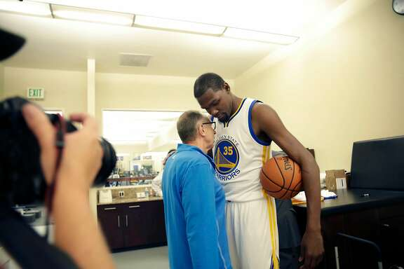 EMBARGOED UNTIL 5PM PER DAN MARTINEZ OF THE WARRIORS ---- Kevin Durant (right) talks with Ron Adams (left), Warriors assistant coach, as he poses for portraits in a Golden State Warriors jersey after the introductory press conference for Durant at the Warriors practice facility on Thursday, July 7, 2016 in Oakland, California.