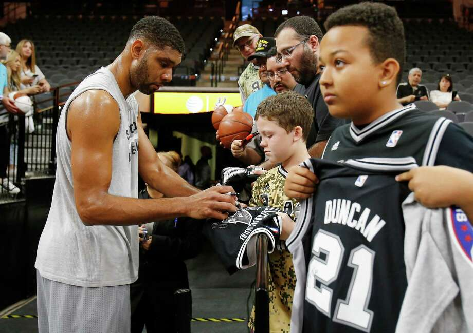 Spurs' Tim Duncan (left) signs autographs for fans before the game against the Miami Heat at the AT&T Center on March 23, 2016. He was voted the best Spur in the Express-News' Readers' Choice. Photo: Kin Man Hui /San Antonio Express-News / ©2016 San Antonio Express-News