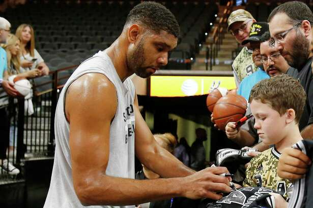 Spurs' Tim Duncan (left) signs autographs for fans before the game against the Miami Heat at the AT&T Center on March 23, 2016. He was voted the best Spur in the Express-News' Readers' Choice.