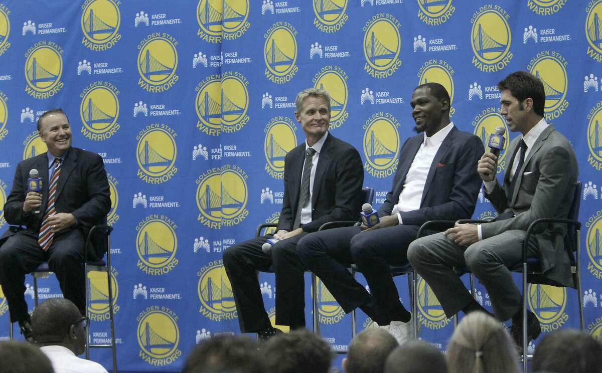 Bob Myers, (right) Warriors general manager, speaks during the introductory press conference for Durant as he sits on stage with Kevin Durant (second from right), Steve Kerr (second from left), Warriors head coach, and Bob Fitzgerald (left) , Warriors play by play announcer at the Warriors practice facility on Thursday, July 7, 2016 in Oakland, California.