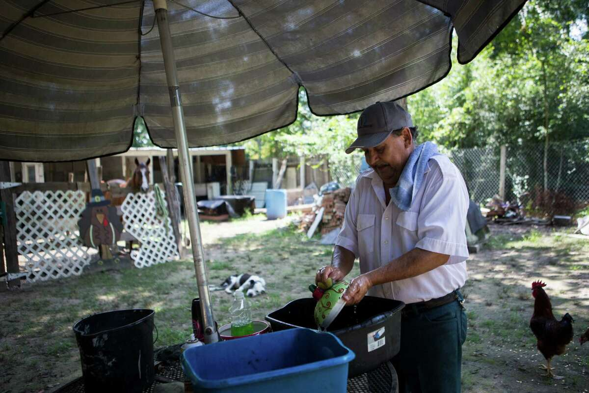 Jose Santos Perez washes dishes using buckets in the backyard of his home in Montgomery County.  He and other families, mostly Latinos, have bought lots and cobbled together dwellings, most which do not have basic services.