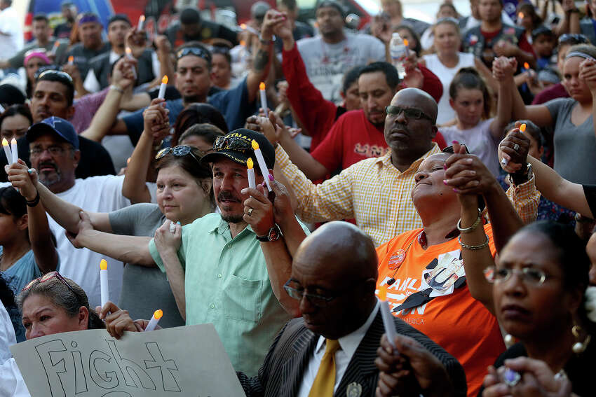 Attendees raise their hands in prayer during the City Wide Prayer Vigil