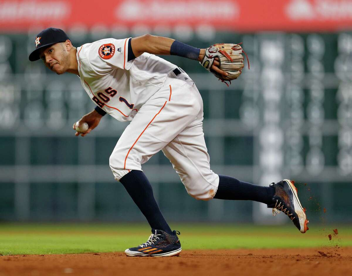 Houston Astros shortstop Carlos Correa (1) throws the ball to first base as Oakland Athletics Yonder Alonso singled during the ninth inning of an MLB baseball game at Minute Maid Park, Thursday, July 7, 2016, in Houston.