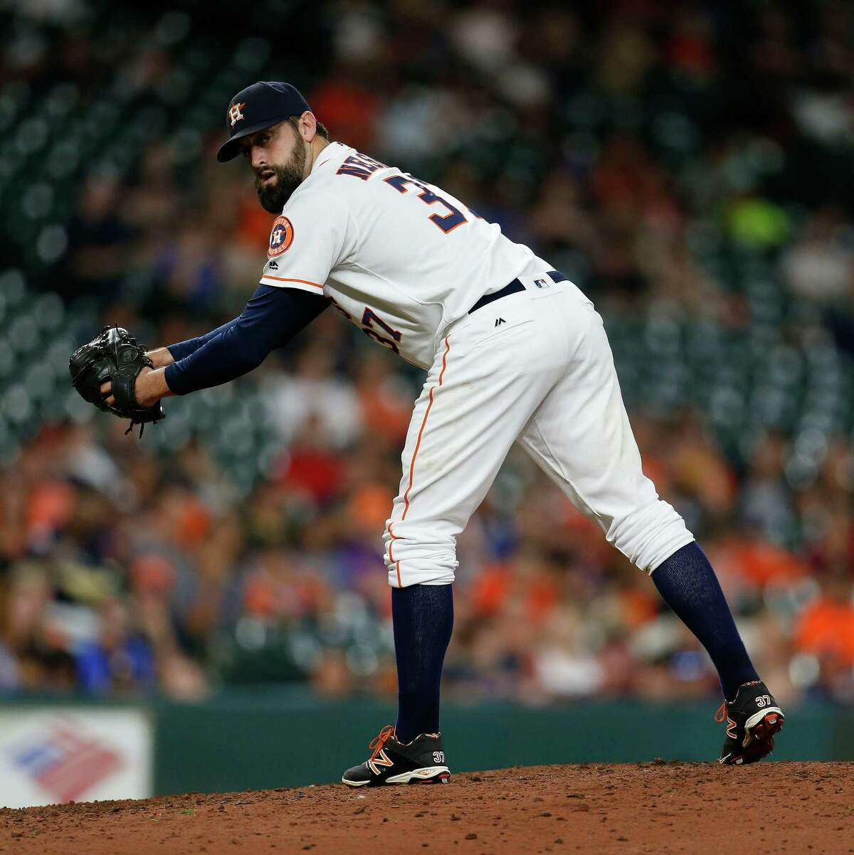 Houston Astros relief pitcher Pat Neshek (37) checks the runner at first base during the ninth inning of an MLB baseball game at Minute Maid Park, Thursday, July 7, 2016, in Houston.
