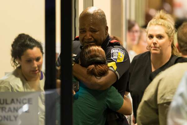 A Dallas Area Rapid Transit police officer receives comfort at the Baylor University Hospital emergency room entrance Thursday, July 7, 2016, in Dallas. Police say one rapid-transit officer has been killed and three injured when gunfire erupted during a protest in downtown Dallas over recent fatal shootings by police in Louisiana and Minnesota.
